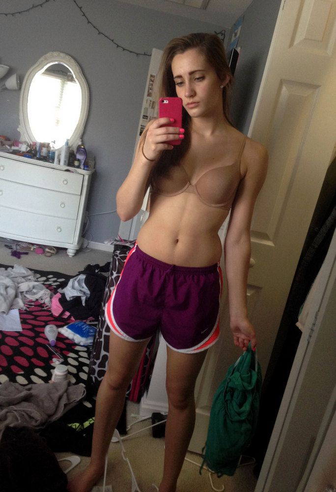 Cheerful teen girlfriends taking pictures naked in the bathroom